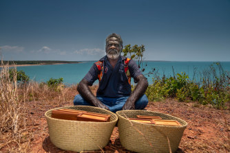 Ross Mandi Wunungmurra,  chair of the  Yalu Marnggithinyaraw Indigenous Corporation, in front of two baskets containing the blood.