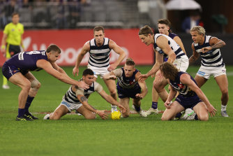 Players fight for the ball at a wet Optus Stadium.