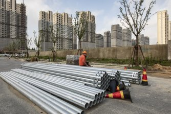 A worker sits on a pile of steel pipes near an under construction residential housing developments in Shanghai, China.