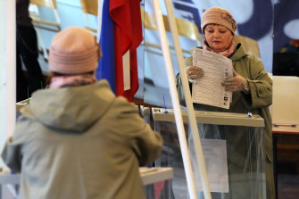 A woman reflected in a mirror casts her ballot during the State Duma, the Lower House of the Russian Parliament and local parliament elections at a polling station in Saint Petersburg, Russia.