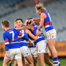 MELBOURNE, AUSTRALIA - JULY 24: Jamarra Ugle-Hagan of the Bulldogs is congratulated by team mates after kicking a goal during the round 20 AFL match between Melbourne Demons and Western Bulldogs at Melbourne Cricket Ground on July 24, 2021 in Melbourne, Australia. (Photo by Quinn Rooney/Getty Images)