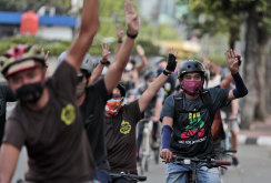 Activists flash a three-finger sign of defiance as they ride bicycles during a solidarity rally against the Myanmar military coup in Jakarta on Saturday.