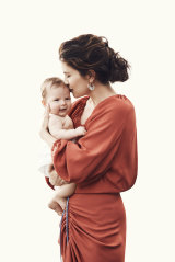 """Higgins poses with baby Luna wearing a Bianca Spender """"Madeline"""" dress and her own earrings."""