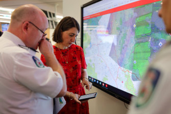 RFS Commissioner Shane Fitzsimmons shows NSW Premier Gladys Berejiklian a map of fire affected areas before a press conference in January.