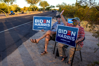 Linda and Tom Rawles, Arizona Republicans for Biden, spend four hours every day outside their home in Carefree, Arizona, holding Biden Harris signs.