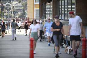 Walkers stroll by Luna Park earlier this month. The park has been closed due to the coronavirus outbreak since mid-March.