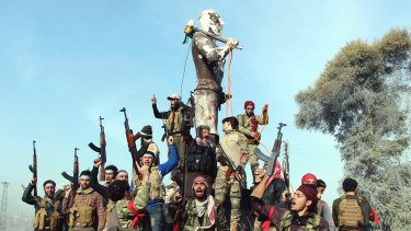 Turkish forces and their allies celebrate around a statue of Kawa, a mythological figure in Kurdish culture, prior to destroying it in the centre of Afrin in Syria.
