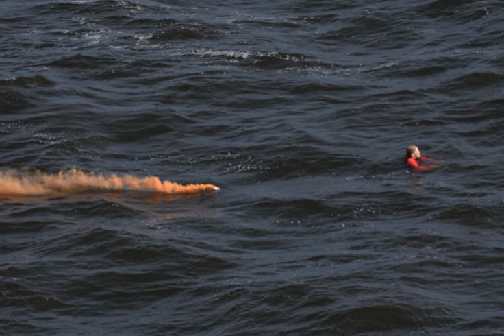 The helicopter released an orange smoke canister near the woman to help direct rescue boats to her.