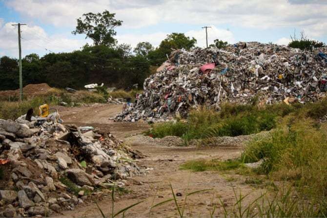 In the background: The white tip of the recycling machine is just visible between the mounds of waste at Cleanaway's Willawong recycling facility. Drivers frequenting the facility said it was rarely seen working.