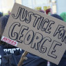 A poster with the inscription 'Justice for George' and 'Antifa on the offensive' is held by a protester demonstrating against police brutality.