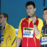 China's Sun Yang, centre, holds up his gold medal with silver medalist Australia's Mack Horton, left, on Sunday.