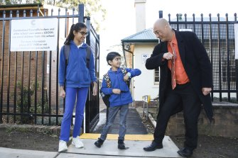 Merrylands East Primary School principal John Goh greets students Maitreyi and brother Yajat Patel at 7.30am.