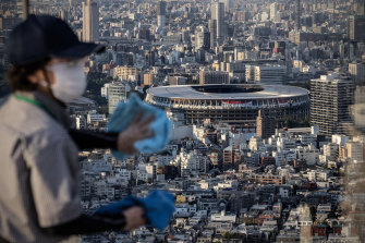 A cleaner wipes a window overlooking the Tokyo Olympic stadium on Shibuya Sky Deck. Home and homeless relocations appear to be a permanent feature of Olympic Games.