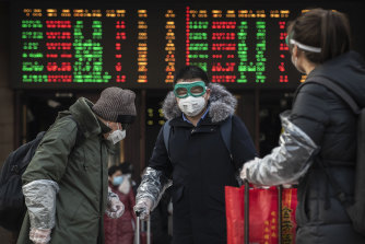 Chinese travellers wear protective masks and goggles after getting off a train in Beijing.