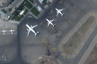 A satellite photo shows swarms of people on the tarmac at Kabul international airport on Monday.