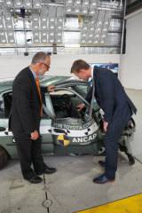 NSW Centre for Road Safety executive director Bernard Carlon and ANCAP chief executive James Goodwin point out the lack of safety features in older cars. Damage to the older vehicle was described as structurally catastrophic.