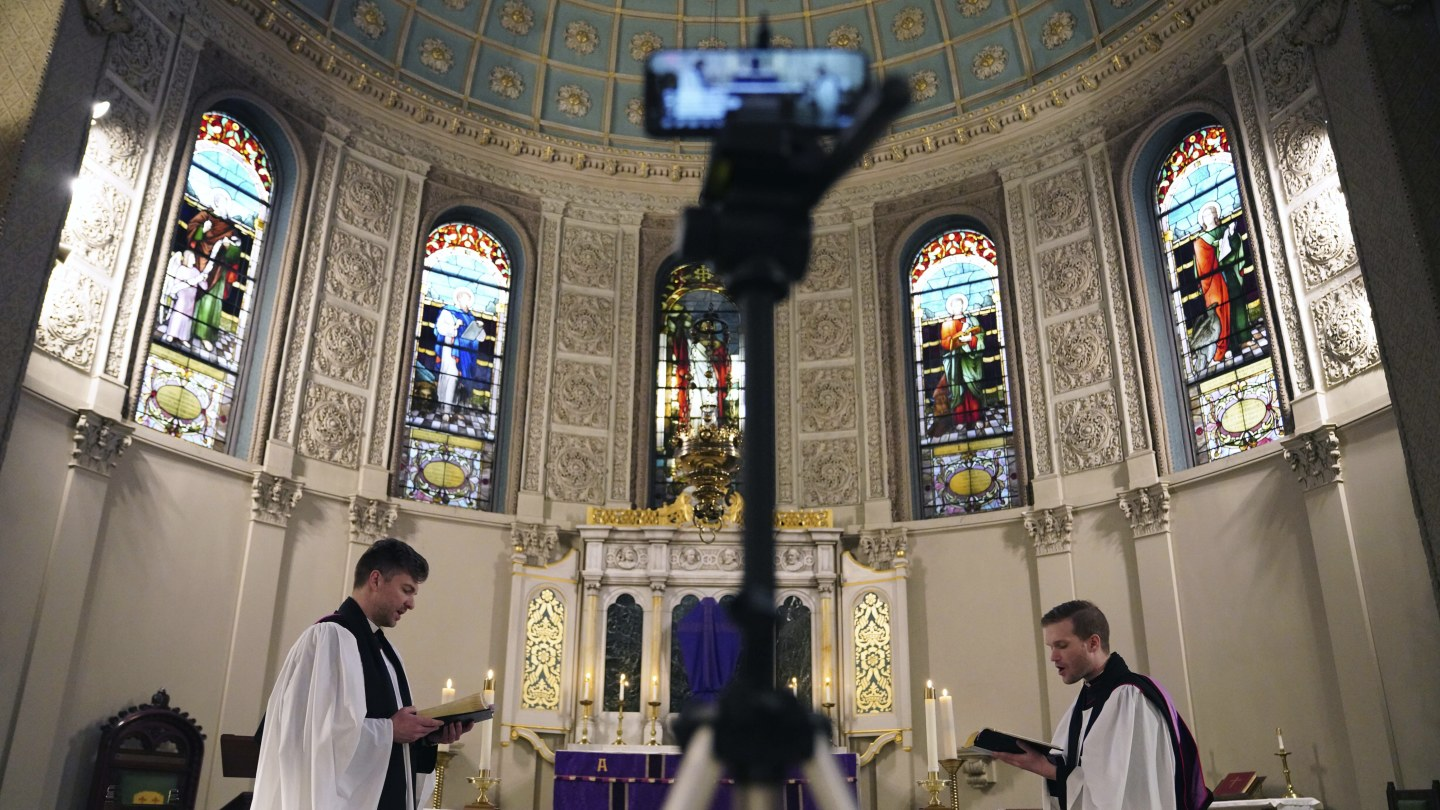 The Rev. Steven Paulikas, right, and curate Spencer Cantrell deliver an Evening Prayer service over Facebook Live in the Brooklyn borough of New York, amid the global COVID-19 coronavirus pandemic.