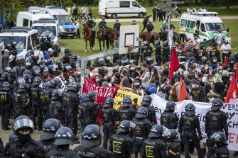 """Demonstrators taking part in a counter-demonstration directed against the demo of the initiative """"Querdenken"""" are surrounded by police units in Karlsruhe, Germany."""