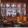 Carrie Lam, center left, prepares to deliver her speech as protestors' slogans are projected on the wall of the Legislative Council.