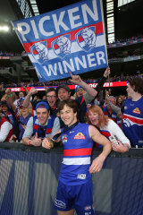 Liam Picken celebrates the 2016 premiership victory with fans.