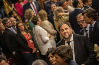Bottom right: Oriol Junqueras, head of the Catalan ERC party, votes under police escort in the May election.