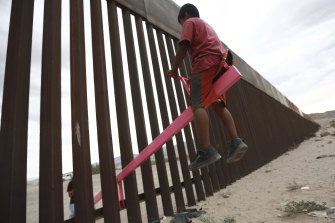 A child plays seesaw installed between the border fence that divides Mexico from the United States in Ciudad de Juarez, Mexico.