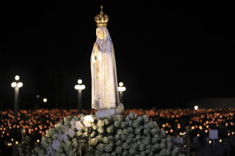 The statue of Our Lady of Fatima is carried past worshippers holding candles in a procession at the Catholic shrine in Fatima, Portugal.