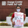 Rachel Bardes holds a sign in front of the Orange County Public Schools headquarters as teachers protest with a car parade around the administration centre in Orlando, Florida.