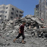 A man walks past the rubble of a building destroyed in an Israeli air strike in Gaza City.