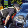 Victoria Police officers stop motorists leaving metropolitan Melbourne at a checkpoint on the border of Sunbury and Gisborne. The spike in cases in Victoria has seen Premier Daniel Andrews declare a state of disaster.