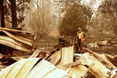 Sarsfield resident Wayne Johnston inspects damage to his property on Friday.