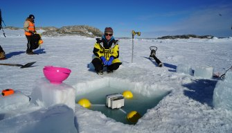 An expeditioner deploys a tide gauge in an ice hole at Casey research station.