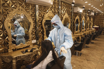 A hairdresser in personal protective suit attends to a customer at a hair salon in New Delhi, India. Businesses and shops reopened in many states as a three-phase plan to lift the nationwide coronavirus lockdown began despite an upward trend in new infections.