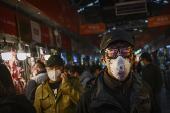 Chinese shoppers wear masks in Beijing. The rate of new coronavirus cases continues to decline in that country.