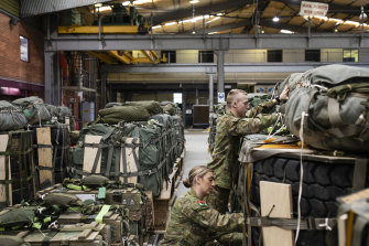 New recruits Private Hannah Gribble and Private Joel Scott check cargo loads that will be dropped by a C130H Hercules during a training mission at the RAAF base at Richmond.