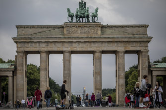 Tourists walk past Brandenburg Gate in Berlin, Germany. Travel restrictions are easing, but look set to be increased for visitors from the United States.