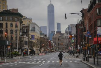 A lone jogger runs on a partially empty 7th Avenue in New York last week.