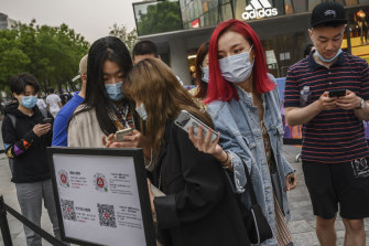 Shoppers scan their local health QR codes from the Beijing Municipality to show security before entering a shopping area.