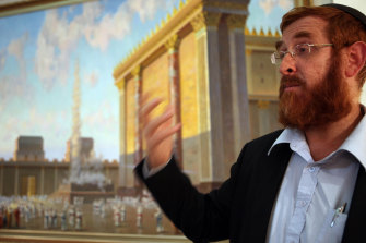 Rabbi Yehuda Glick stands next to an artist's impression of the Jewish Temple, deemed to have stood on what is now the site of al-Aqsa mosque.
