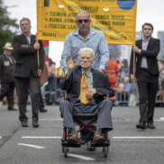 99-year-old Noel's on wheels these days but he's still a marching man