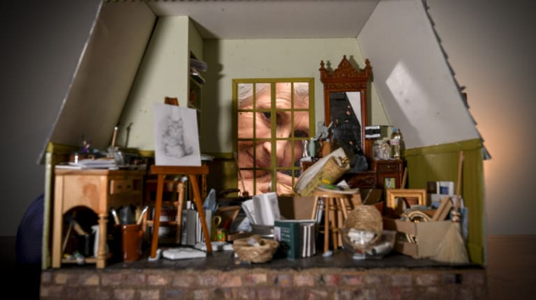 Portal to a magical world: Lyn Mallett (through window) makes free minature rooms - here an artist's studio - for children orphaned or abandoned by drug addict parents.