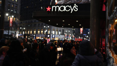 Pedestrians pass in front of a Macy's Inc. department store in New York.