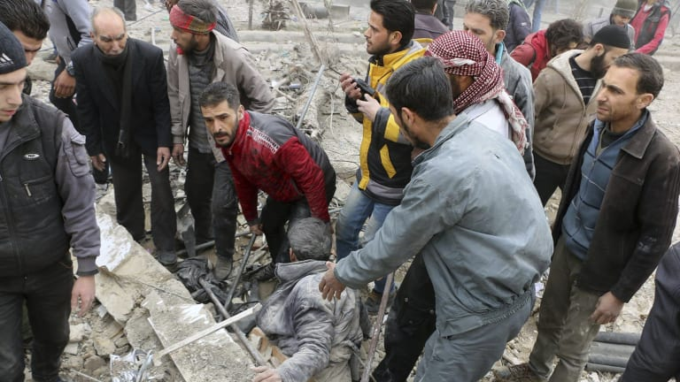 Men pull a survivor from the rubble after airstrikes hit a rebel-held suburb near Damascus on  Monday.