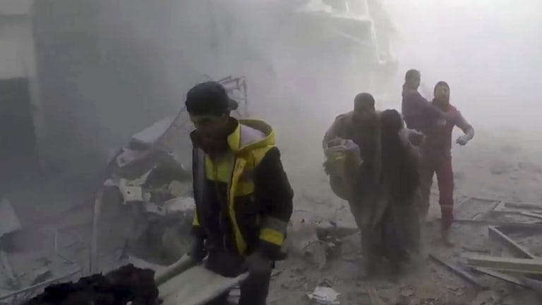 A frame from a video released on Saturday, February 24 shows White Helmets helping residents during airstrikes and shelling by Syrian government forces, in Ghouta, a suburb in Damascus.