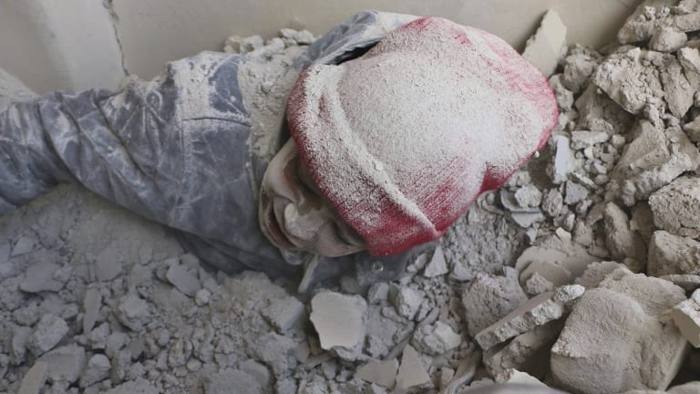 This photo provided by the Syrian Civil Defense group known as the White Helmets, shows a child partly buried in rubble after airstrikes hit a rebel-held suburb near Damascus on Monday.
