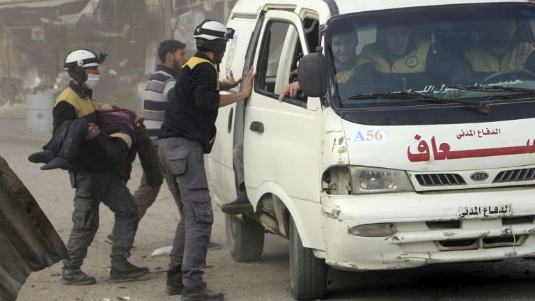 A civil defence worker carrying a victim after airstrikes hit a rebel-held suburb near Damascus on  Thursday.