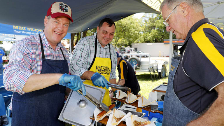 Queensland Opposition Leader Tim Nicholls helps out with a sausage sizzle during a visit to Redland Bay market on Sunday.