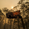 The Australian flag on a property at Oakdale with smoke from the bushfire approaches.