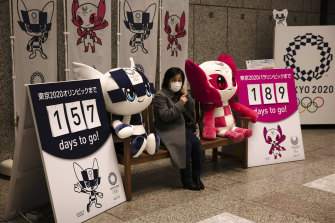 A woman wearing a face mask has her photo taken with the Olympic mascots in Tokyo.