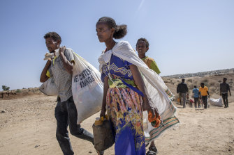 Tigray refugees who fled the conflict in the Ethiopia's Tigray walk to Hamdeyat Transition Center after arriving on the banks of the Tekeze River on the Sudan-Ethiopia border, in Hamdayet, eastern Sudan, Saturday, November 21.